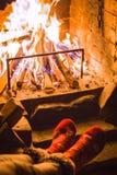 Meisje in warme sokken warme benen dichtbij de open haard Rust, ontspanning dichtbij de open haard in de winter Comfortabele de w royalty-vrije stock foto