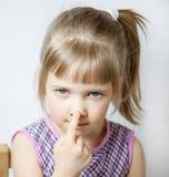 Meisje wat betreft haar neus stock foto's