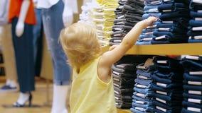 Meisje wat betreft jeans die op planken in kledingsopslag liggen stock video