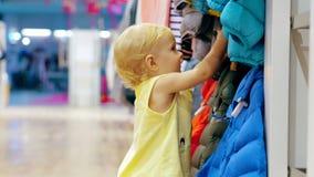 Meisje wat betreft kleren in de kledingsopslag van kinderen tijdens familie het winkelen stock video
