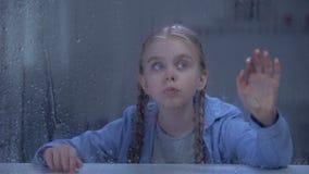 Meisje wat betreft regenachtig die venster, door donder bang wordt gemaakt, slechte weersomstandigheden stock videobeelden