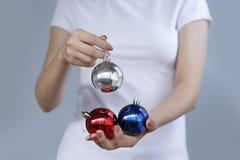 Meisje in wit Kerstmisstuk speelgoed drie van de t-shirtholding bal Zilver, Royalty-vrije Stock Foto's