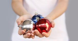 Meisje in wit Kerstmisstuk speelgoed drie van de t-shirtholding bal Zilver, Royalty-vrije Stock Foto