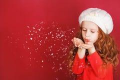 Meisje in witte hoeden blazende sneeuw met haar hand stock afbeelding