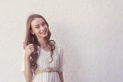Meisje in witte kleding die duim tonen royalty-vrije stock afbeelding