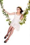 Meisje in witte kleding die op bloemschommeling slingert. Royalty-vrije Stock Afbeeldingen