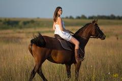 Meisje in witte kleding die op een paard berijden Royalty-vrije Stock Foto