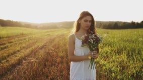 Meisje in witte kleding die zich in weide met boeket die van wilde bloemen bij zonsondergang bevinden, camera bekijken stock footage