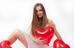 Meisje in witte kleding met hart-vormig baloons stock fotografie