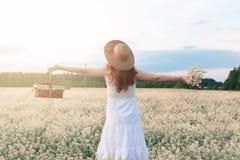 Meisje in witte kleding op een gebied van het gele bloemen tot bloei komen Stock Afbeeldingen