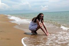 Meisje in witte kleding op het strand stock foto