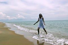 Meisje in witte kleding op het strand stock foto's
