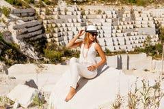 Meisje in witte kleren die op witte marmeren steengroeve, mening aan de kant stellen Royalty-vrije Stock Foto's