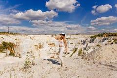 Meisje in witte kostuum en hoed in volledige lengte, marmeren steengroeve, wit marmer Stock Foto