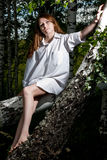 Meisje in witte overhemdszitting op de boom Royalty-vrije Stock Afbeeldingen