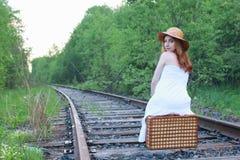 Meisje in witte sundress en rieten koffer die op sporen lopen Stock Afbeelding