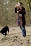 Meisje, zeepbels en natte zwarte hond stock afbeelding