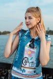 Meisje in zonnebril, jeansborrels en een jasje die zich in een zonnig helder licht bevinden Royalty-vrije Stock Afbeelding