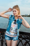 Meisje in zonnebril, jeansborrels en een jasje die zich in een zonnig helder licht bevinden Royalty-vrije Stock Afbeeldingen