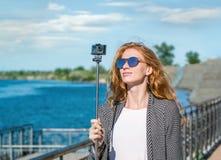 Meisje in zonnebril met de gangen van de actiecamera langs de promenade Stock Foto