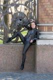 Meisje in zwarte bij de omheining Stock Afbeeldingen