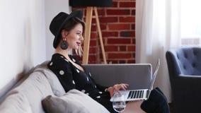 Meisje in zwarte hoed en kledingszitting in een bank met laptop stock videobeelden