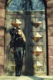 Meisje in zwarte status dichtbij oude houten deur Stock Afbeelding