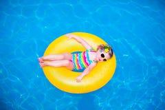 Meisje in zwembad op opblaasbare ring Stock Fotografie
