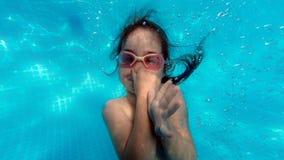 Meisje zwemmen onderwater in pool stock foto