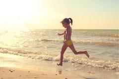 Meisje in zwempaklooppas langs de kust van het overzees Gestemd beeld stock afbeelding