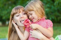 Meisjeaandelen met haar moederlolly Royalty-vrije Stock Fotografie