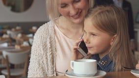 Meisjebesprekingen op de telefoon bij de koffie stock footage