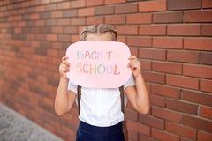 Meisjeblonde in school eenvormige tribunes dichtbij een bakstenen muur die een bord met de tekst terug naar school houdt stock afbeelding