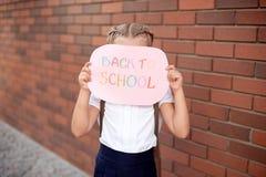 Meisjeblonde in school eenvormige tribunes dichtbij een bakstenen muur die een bord met de tekst terug naar school houdt royalty-vrije stock afbeeldingen
