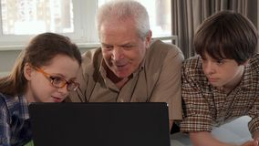 Meisjehulp haar opa op laptop te typen royalty-vrije stock afbeeldingen