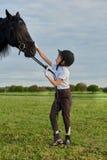 Meisjejockey die met haar zwart paard in professionele uitrusting communiceren Stock Foto's