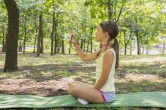 Meisjekind die van 8 jaar camerazitting bekijken op groen gazon in stadspark meisje 8 jaar in het park die beelden van nationaal  royalty-vrije stock fotografie
