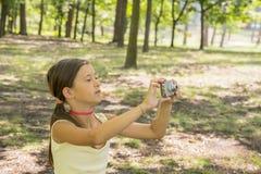 Meisjekind die van 8 jaar camerazitting bekijken op groen gazon in stadspark meisje 8 jaar in het park die beelden van nationaal  stock afbeeldingen