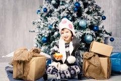 Meisjekind die van die vijf jaar op de vloer dichtbij Kerstboom zitten met speelgoed, ballen wordt verfraaid In de handen houdt e royalty-vrije stock fotografie