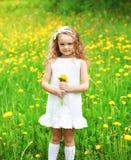 Meisjekind in openlucht op het gras met gele paardebloem Stock Fotografie