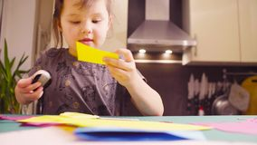Meisjeknipsel gekleurd document met schaar stock videobeelden