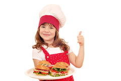 Meisjekok met omhoog sandwiches en duim stock afbeelding