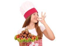 Meisjekok met vleesballetjes op plaat en o.k. handteken stock fotografie