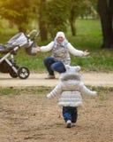 Meisjelooppas aan haar mamma met een babywandelwagen in parkland Mamma en dochterbereik uit aan elkaar stock afbeelding