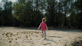Meisjelooppas over het zand in een bos stock video