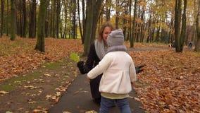 Meisjemeisje die aan haar mamma in de herfstpark lopen Gelukkige mensen die tegen gevallen bladerenachtergrond koesteren 4K stead stock videobeelden