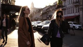 Meisjes beste vrienden die handen en het lopen houden Achtermening van twee vrolijke meisjes die samen op de bestrating in lopen stock footage