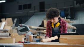 Meisjes bezig oppoetsend hout met schurend blok in werkplaats in houtworkshop stock video