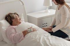 Meisjes bezoekende grootmoeder bij het ziekenhuis Stock Fotografie
