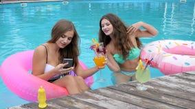 Meisjes bij badpakken met cocktails in handen op mobiele, beeldentelefoon van vrienden bij zwempakken worden gefotografeerd dat stock videobeelden